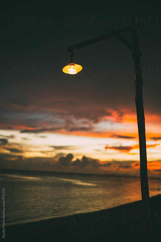 Lamp on the beach against sunset background. by Studio Firma for Stocksy United