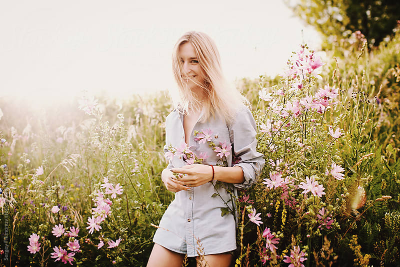 Beautiful young girl walking in the lush spring field and laughs by Sergey Filimonov for Stocksy United