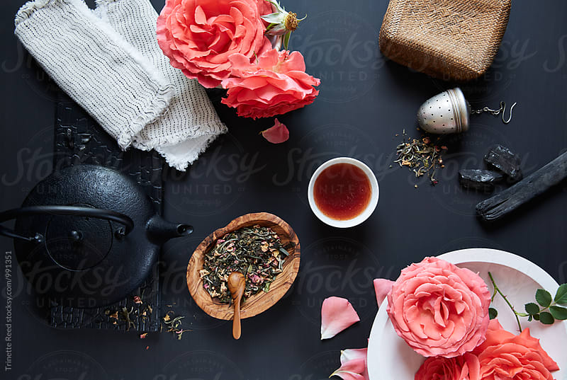 Green tea with dried roses in it on table  by Trinette Reed for Stocksy United
