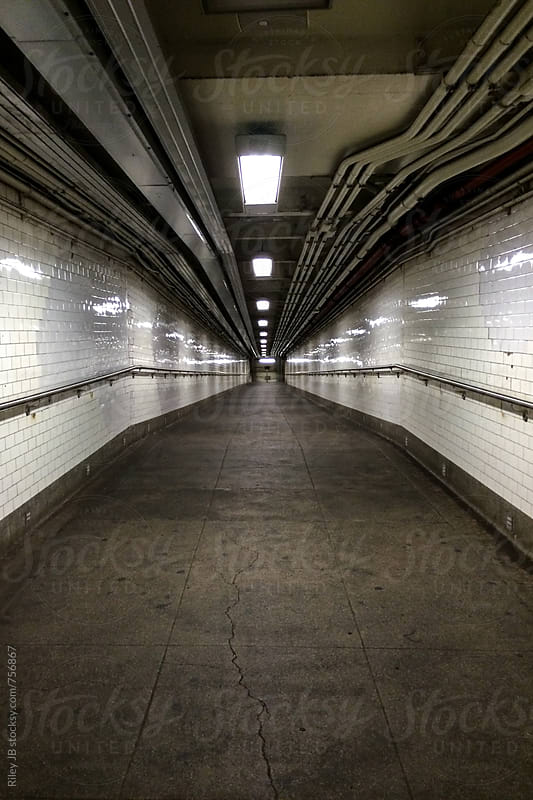 An empty, gritty walkway into a NYC subway station by Riley Joseph for Stocksy United