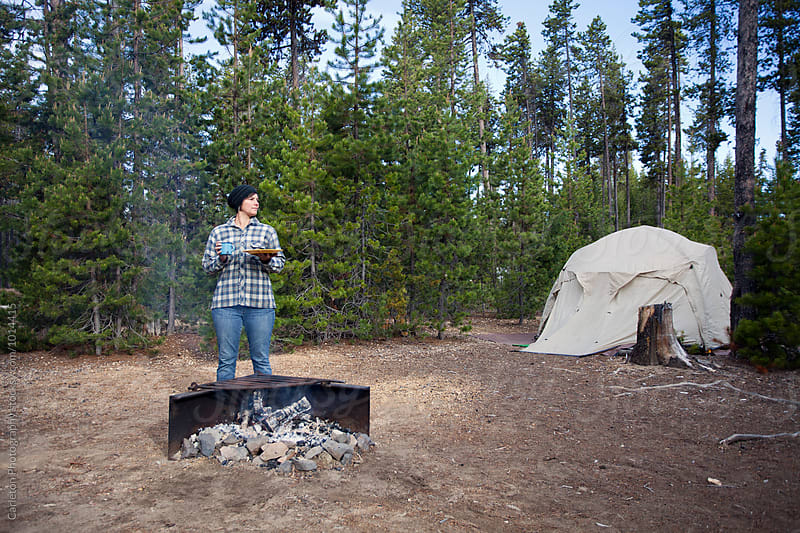 Woman in plaid flannel shirt and jeans has breakfast next to a campfire by Carleton Photography for Stocksy United