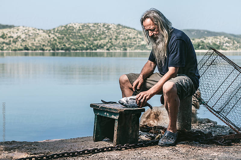 portrait of an old fishermen with long hair and white beard cutting a freshly caught fish by Leander Nardin for Stocksy United