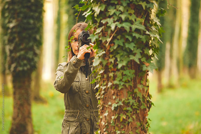Woman with film camera is behind a tree. Autumnal forest. by BONNINSTUDIO for Stocksy United