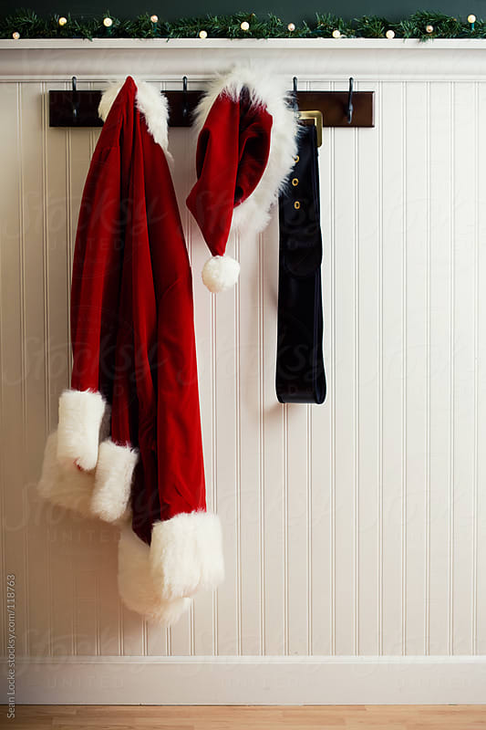 Christmas: Santa Coat And Hat Hanging On Rack by Sean Locke for Stocksy United