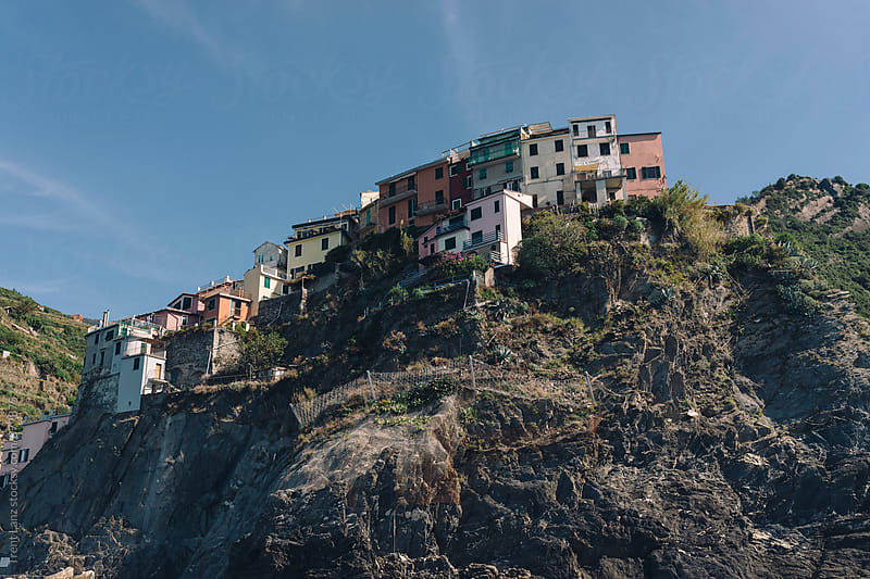 View of houses on cliff in Cinque Terre fishing village by Trent Lanz for Stocksy United