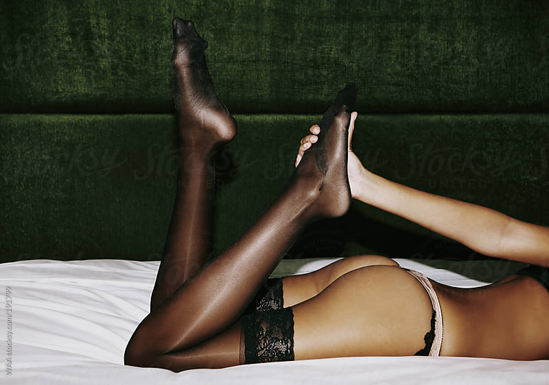 Woman In Stockings Lying On Bed by WAA for Stocksy United