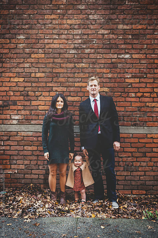 Cute, dressed up parents and little girl looking  at camera in fall and little girl looking  at camera in fall by Rob and Julia Campbell for Stocksy United