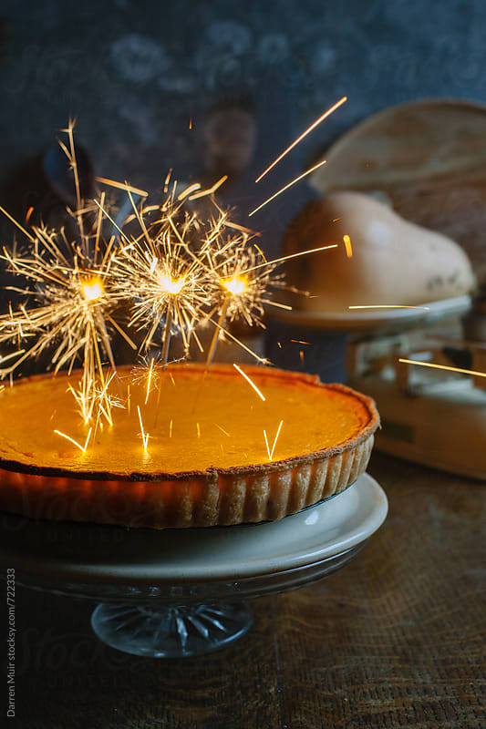 Pumpkin pie with sparklers.  by Darren Muir for Stocksy United