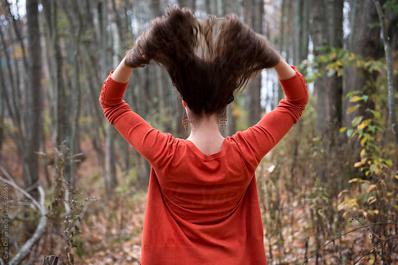 Woman flips her hair in the forest by Cara Slifka for Stocksy United