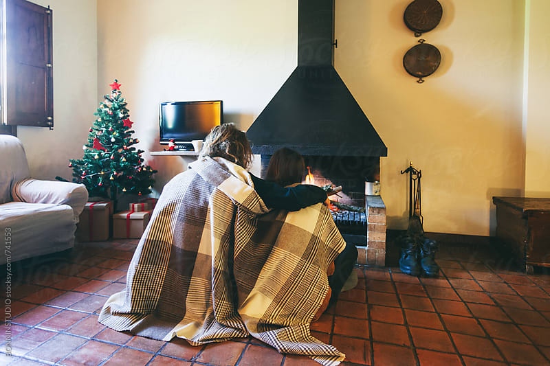 Back view of a couple covering with a blanket by the fireplace. by BONNINSTUDIO for Stocksy United