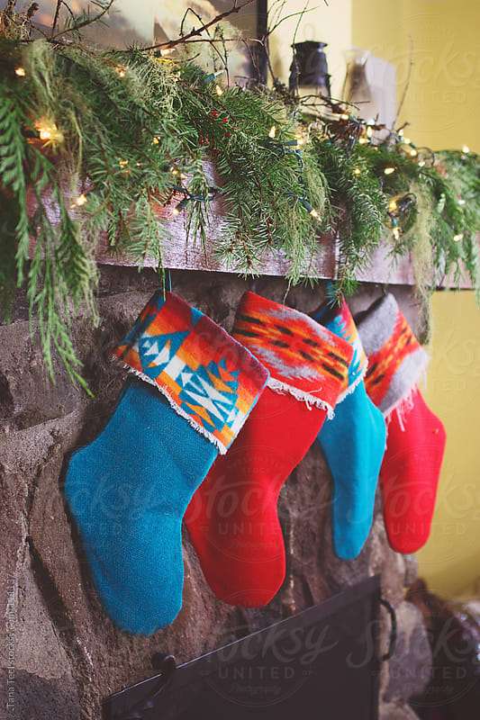 Christmas stockings hung from the fireplace mantle by Tana Teel for Stocksy United