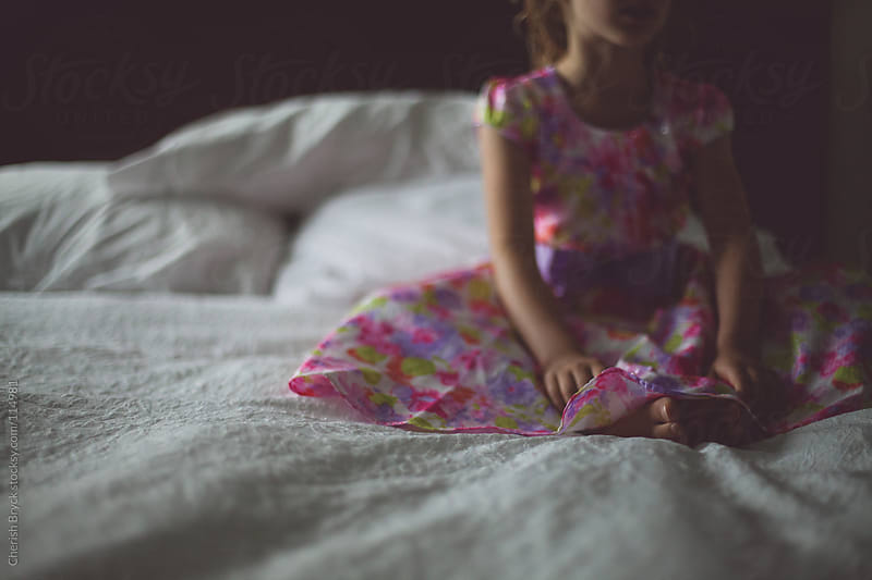 LIttle girl in her party dress sits still on the bed. by Cherish Bryck for Stocksy United