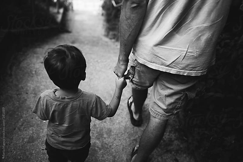 father and son hold hands by Maria Manco for Stocksy United