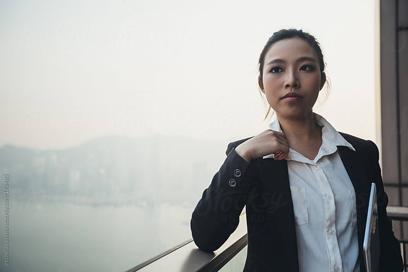 Young asian businesswoman holding a digital tablet by michela ravasio for Stocksy United