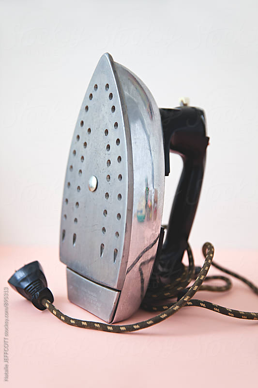 A retro household iron against a pink and white background by Natalie JEFFCOTT for Stocksy United