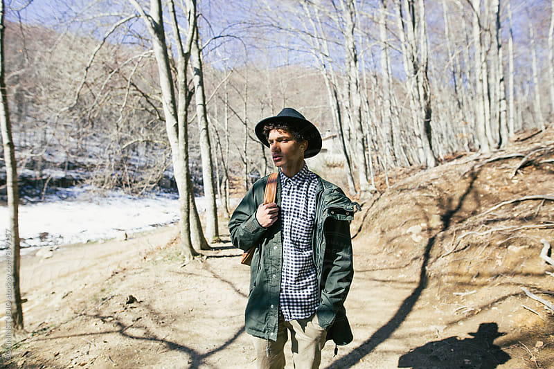Mountaineer walking in the woods on a sunny day. by BONNINSTUDIO for Stocksy United