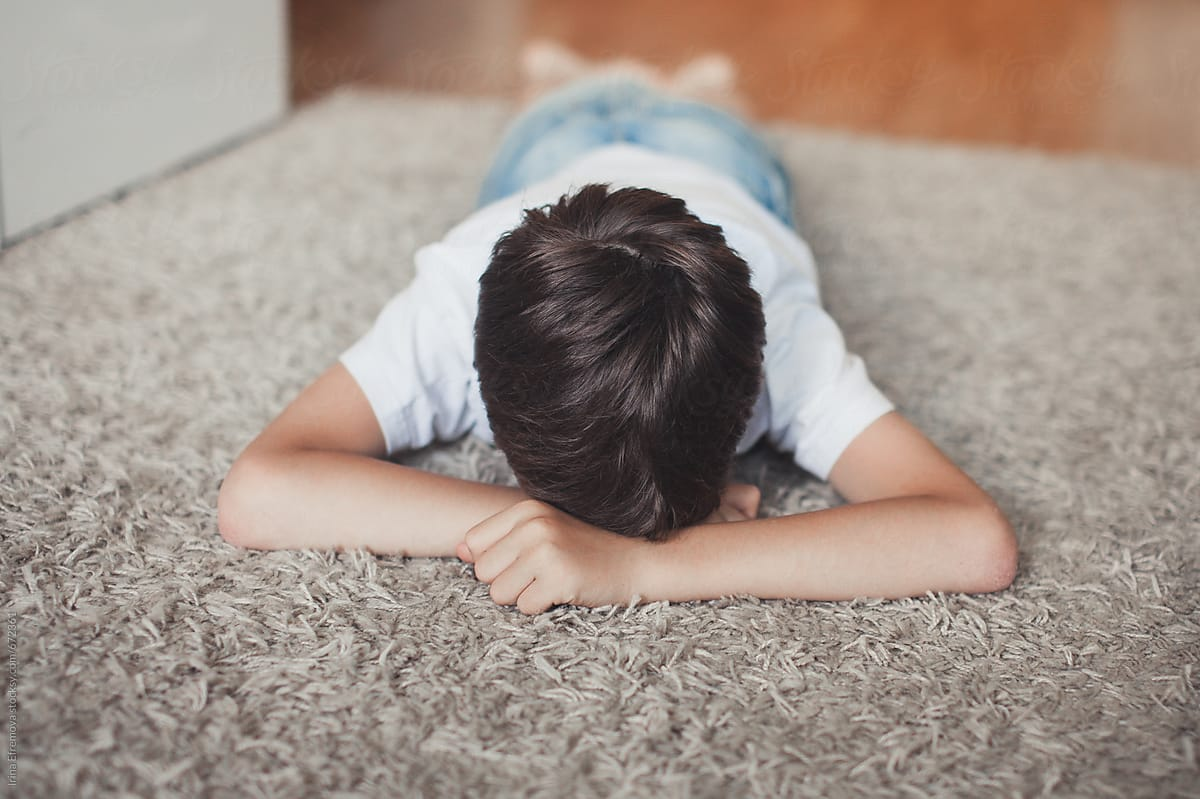 Young boy laying upset on the floor by