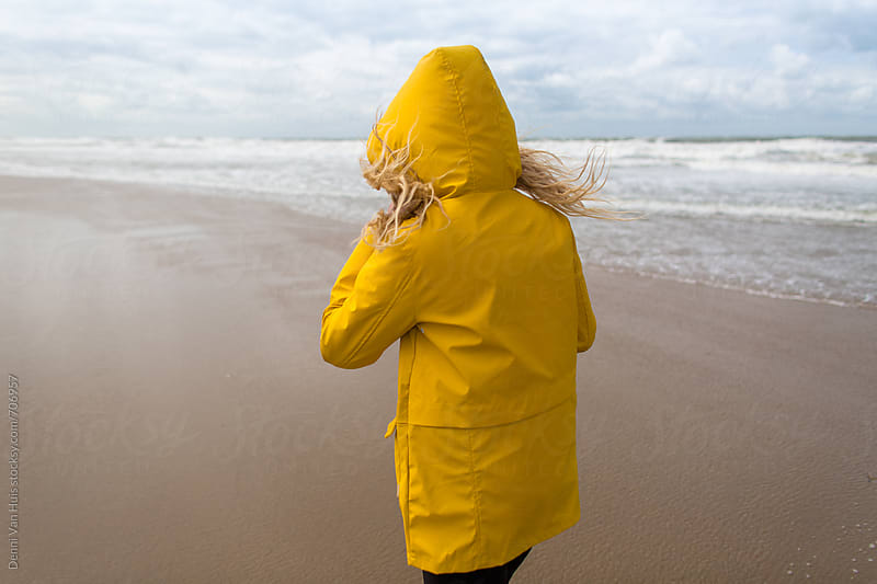 Woman on a windy beach wearing a yellow raincoat. by Denni Van Huis for Stocksy United