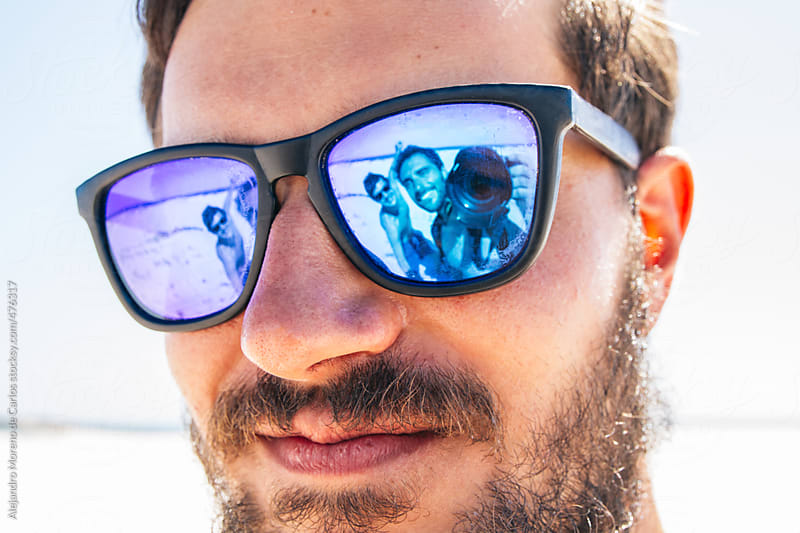 Young hipster man portrait with his happy friends showing on the reflection of his sunglasses by Alejandro Moreno de Carlos for Stocksy United