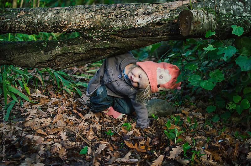 Little girl climbing under a log by Dominique Chapman for Stocksy United