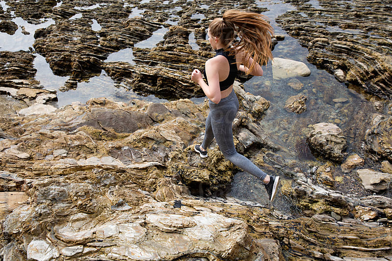 Athletic female running on rocks at the beach by Curtis Kim for Stocksy United