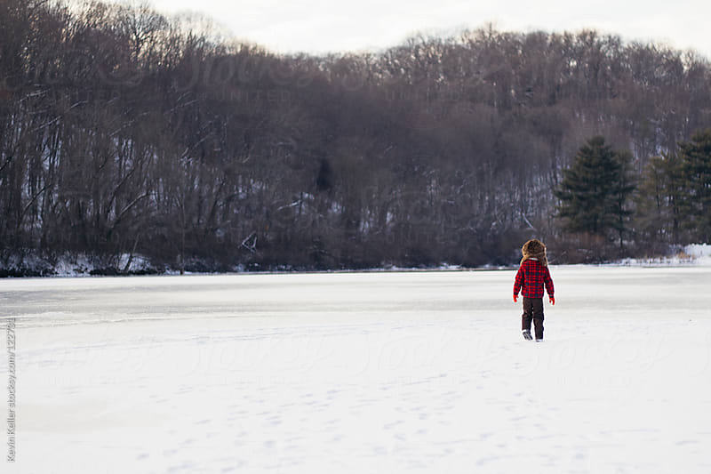 Wide Shot of a Young Boy Walking on a Frozen Lake by Kevin Keller for Stocksy United