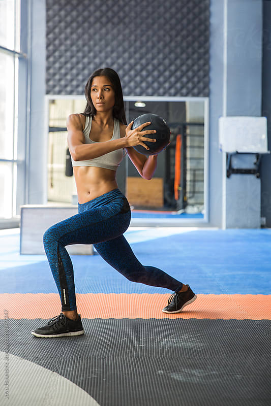 Fit woman working out with a medicine ball by Jovo Jovanovic for Stocksy United