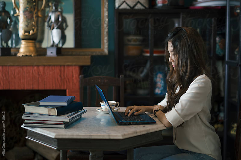 Young lady working from home by Alita Ong for Stocksy United