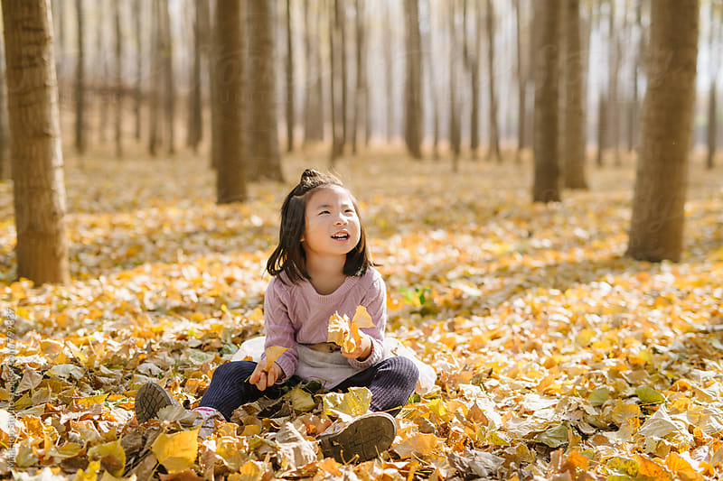 Young girl playing leaf in autumn wood by MaaHoo Studio for Stocksy United