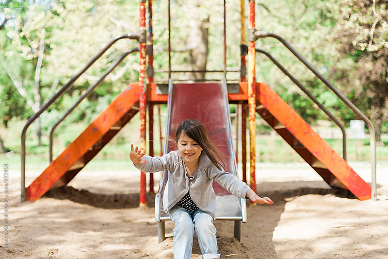 Happy girl sliding at the playground by Amanda Worrall for Stocksy United