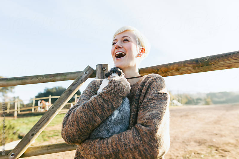 Laughing woman holding a cute bunny on farm. by BONNINSTUDIO for Stocksy United