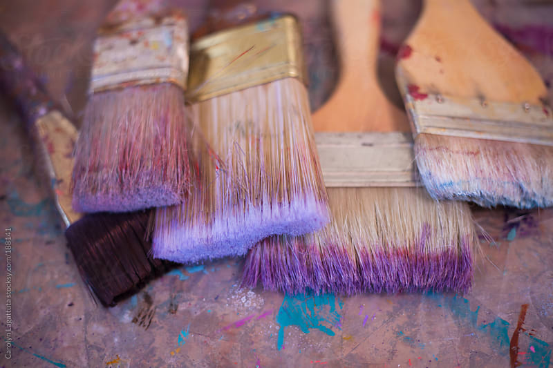 Close up of well loved paint brushed stained with purple paint by Carolyn Lagattuta for Stocksy United