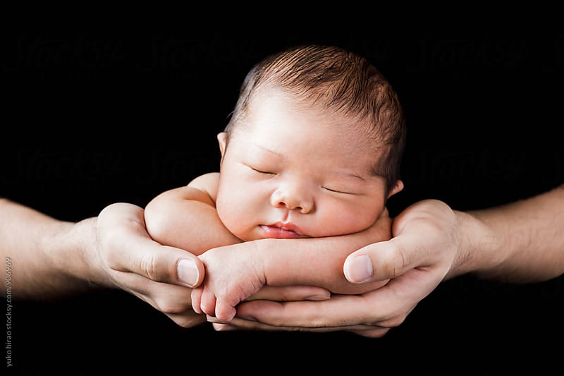 Sleeping baby in father's' hands in black background by yuko hirao for Stocksy United