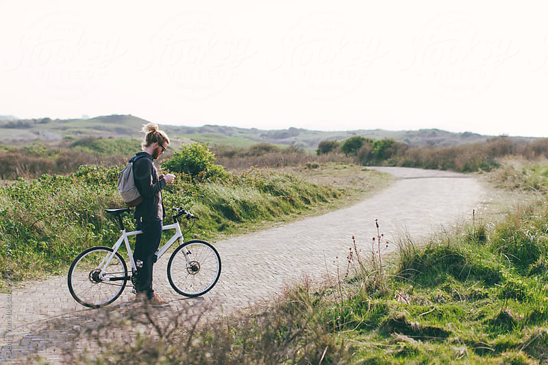 Man standing still with bicycle to set a timer.  by Denni Van Huis for Stocksy United
