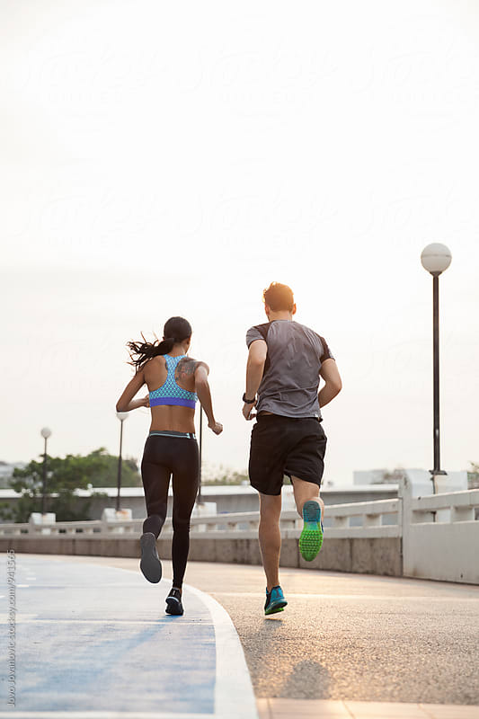 Young couple running together by Jovo Jovanovic for Stocksy United