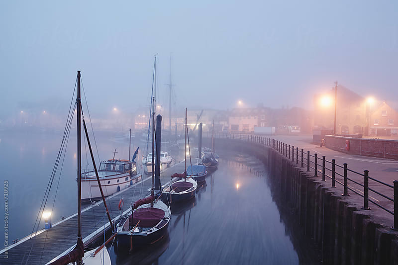 Boats moored in the harbour in fog at dawn. Wells-next-the-sea, Norfolk, UK. by Liam Grant for Stocksy United