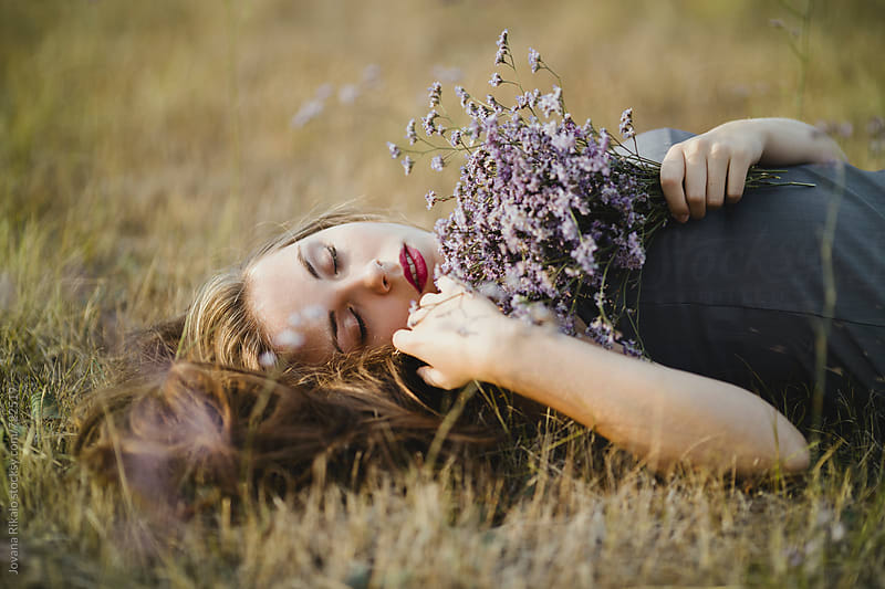 Beautiful young woman lying on grass and holding flower bouquet by Jovana Rikalo for Stocksy United