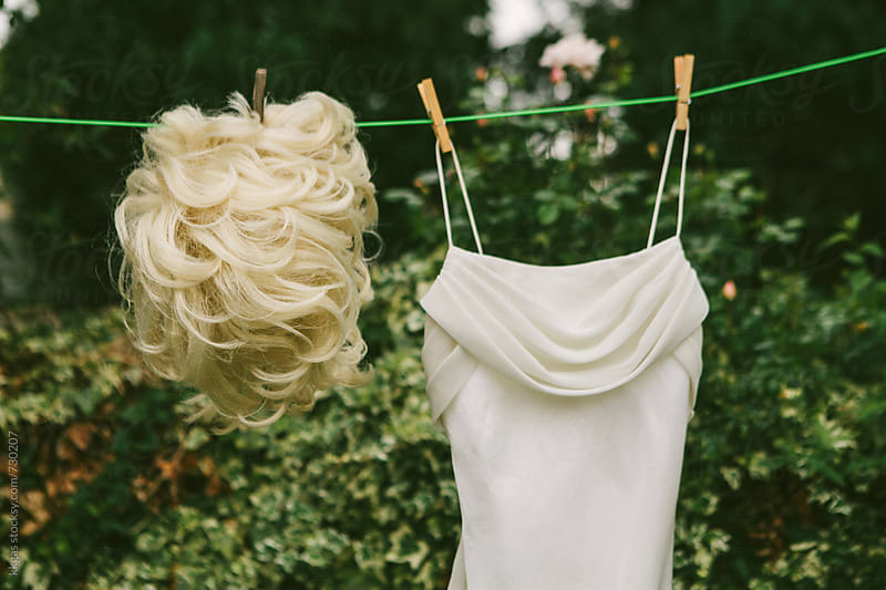 Blonde wig and white dress hanging on a washing line to dry by kkgas for Stocksy United