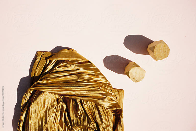 Golden material and two wooden pieces in a composition on the pink paper. by Nina Zivkovic for Stocksy United