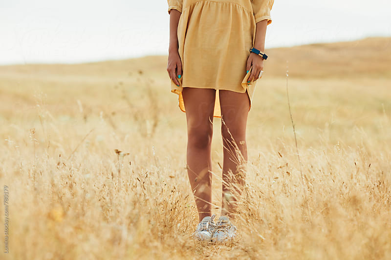 Woman in a Yellow Dress Standing Outdoors by Lumina for Stocksy United