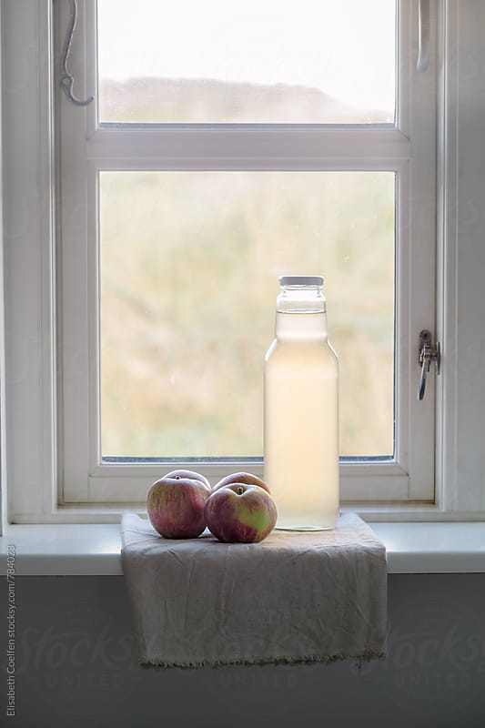 Wooden window with fresh local apple juice and apples by Elisabeth Coelfen for Stocksy United
