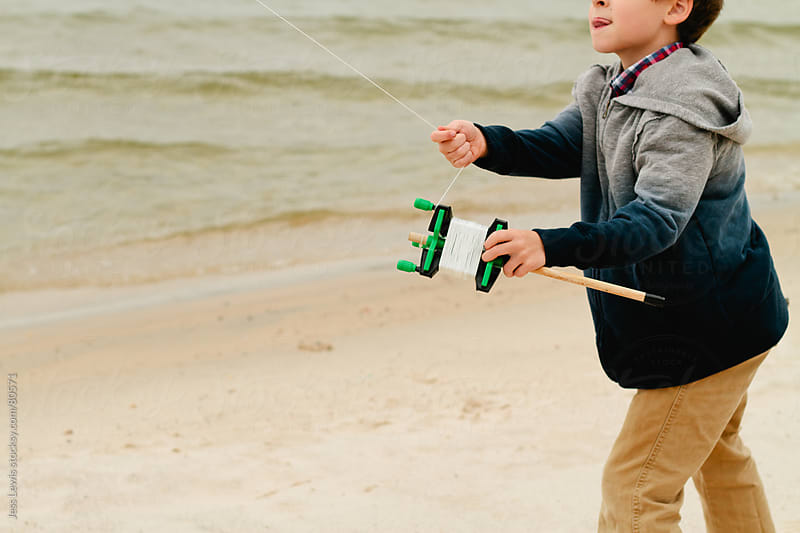 boy holding kite reel and line by Jess Lewis for Stocksy United