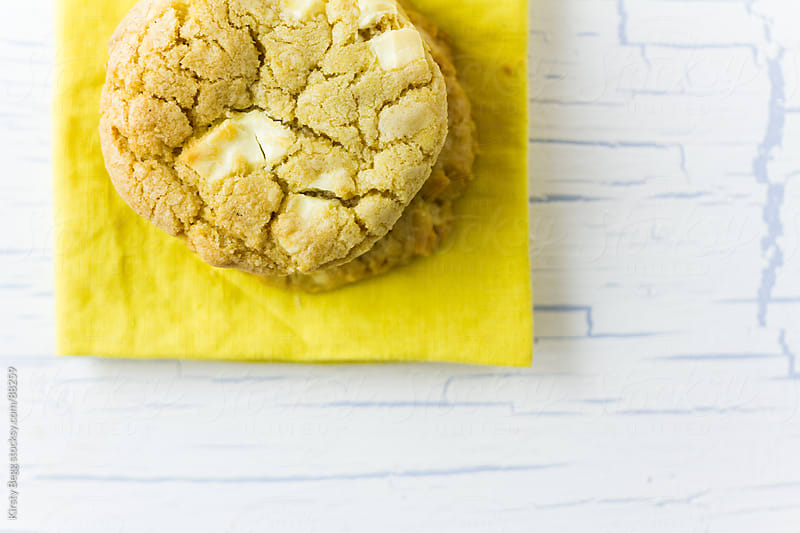 Stack of white chocolate cookies fro above on yellow napkin by Kirsty Begg for Stocksy United