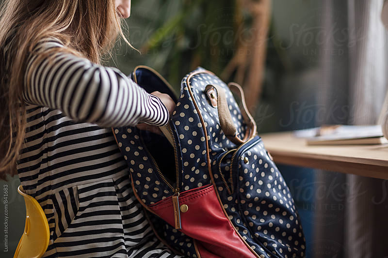 Girl Putting a Book Into her Bag by Lumina for Stocksy United