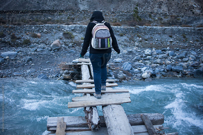 Crossing a wooden bridge. by Shikhar Bhattarai for Stocksy United