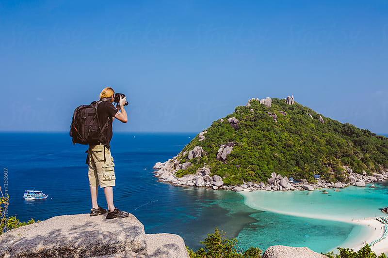 Man photographing tropical island getaway with a sand beach by Soren Egeberg for Stocksy United