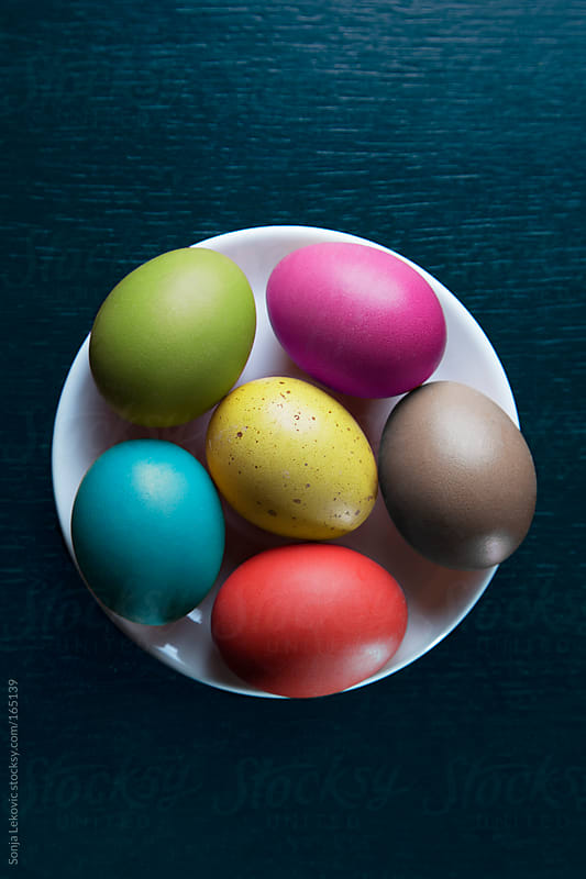 colored easter eggs on black table by Sonja Lekovic for Stocksy United