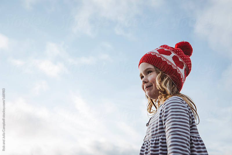 young girl looking out with sky and cloud background by Rob and Julia Campbell for Stocksy United