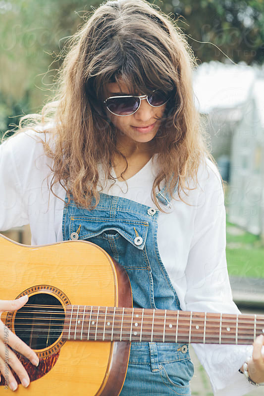 Young woman playing guitar outdoors  by kkgas for Stocksy United