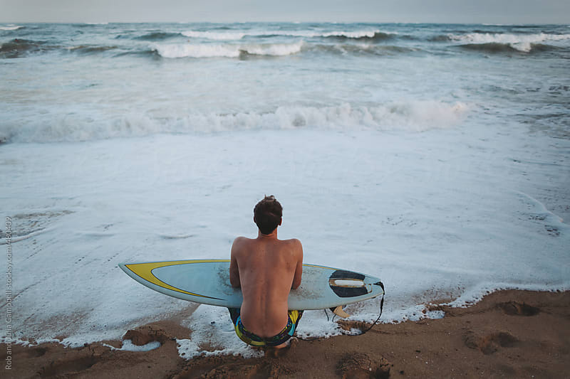 Man sitting with surfboard on beach - watching waves by Rob and Julia Campbell for Stocksy United